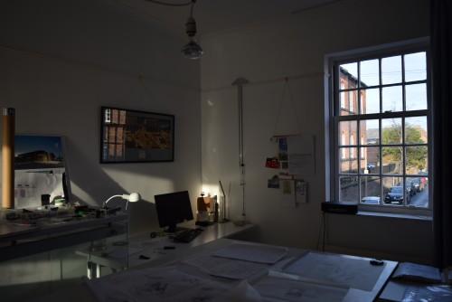 Architects Studio Macclesfield. Interior view showing sunlight falling onto desk beside window onto sunlit street.