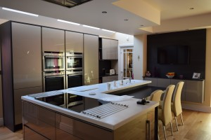 Interior view of Sale kitchen showing white work top with induction hob and flush extractore plate overhead typical of designer kitchens in Sale.
