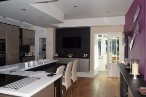 Interior view of Sale kitchen looking out to sunny conservatory and garden room beyond typical of designer kitchens in Sale.